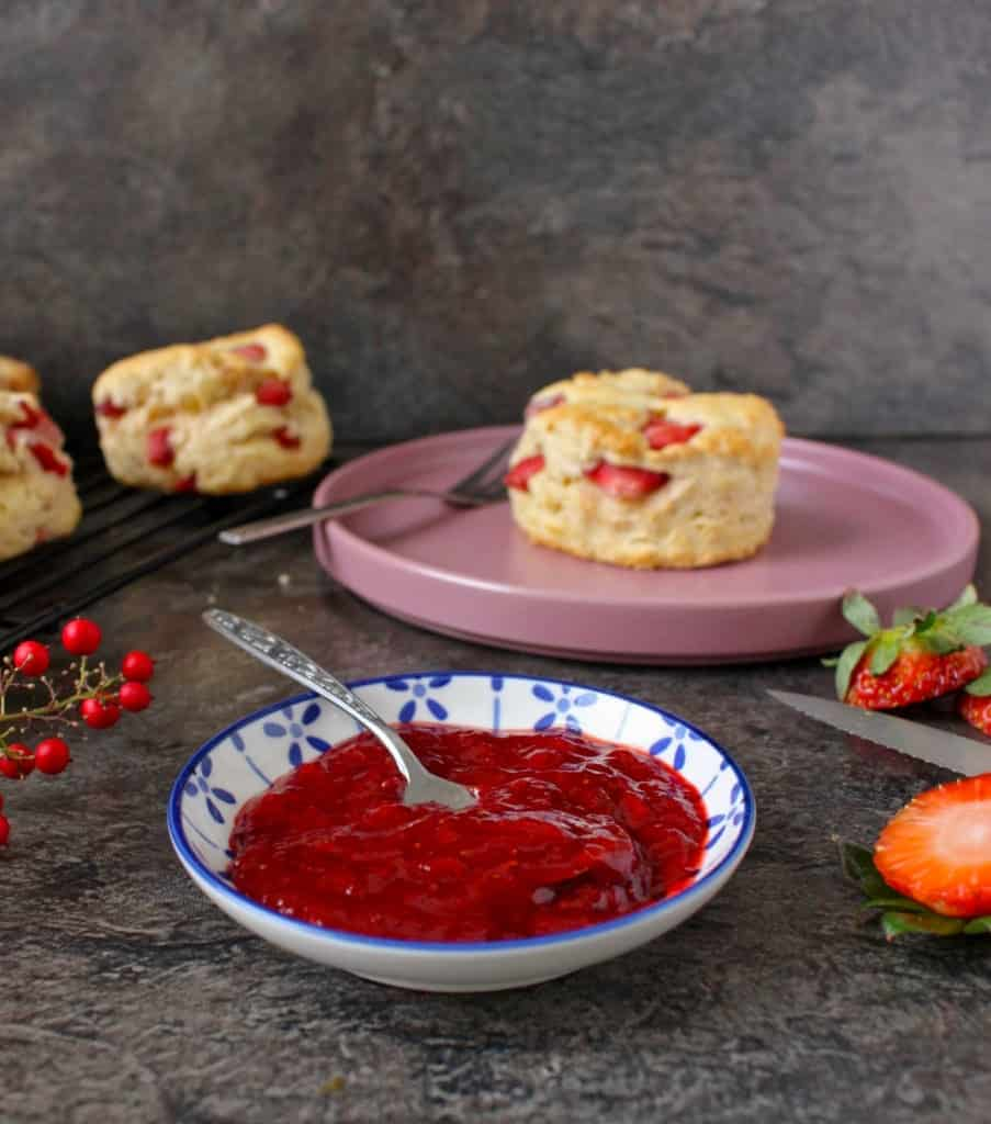Strawberry Jam in a small bowl with scones in the background