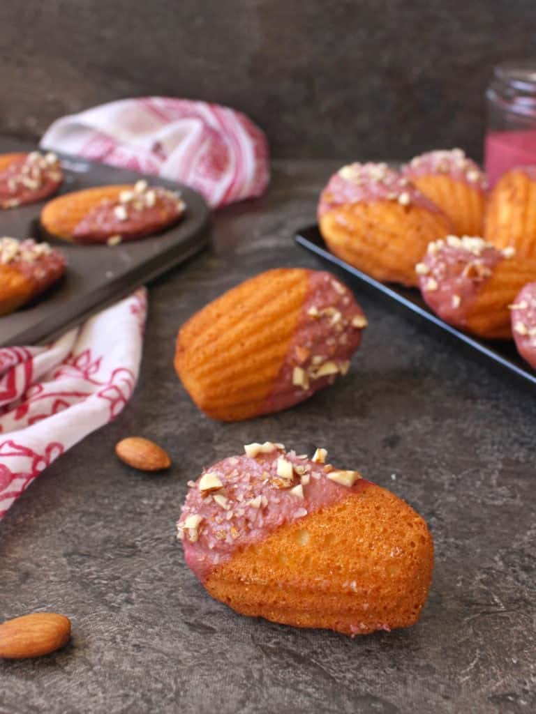 One madeleine on its side on a grey surface with almonds.