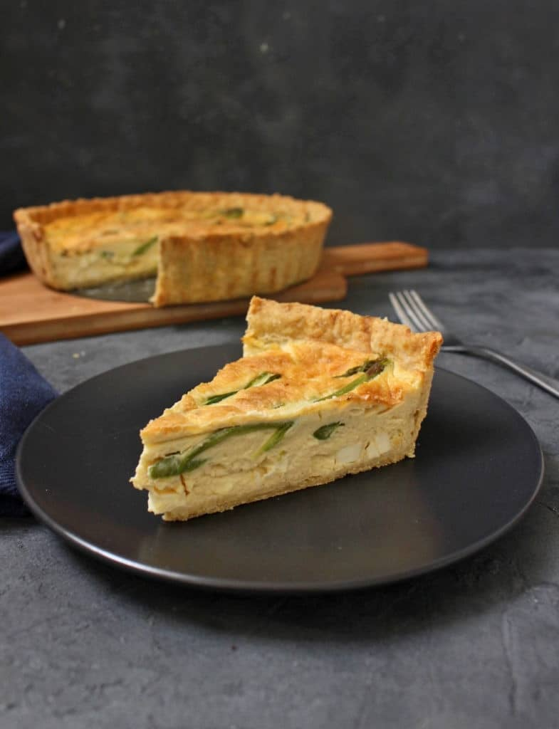 One slice of quiche on a black plate