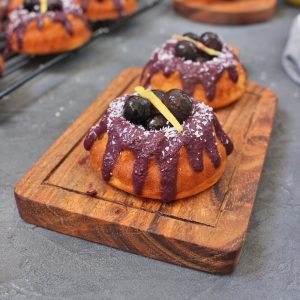 Two Lemon Blueberry Mini Bundt Cakes on a wooden serving board