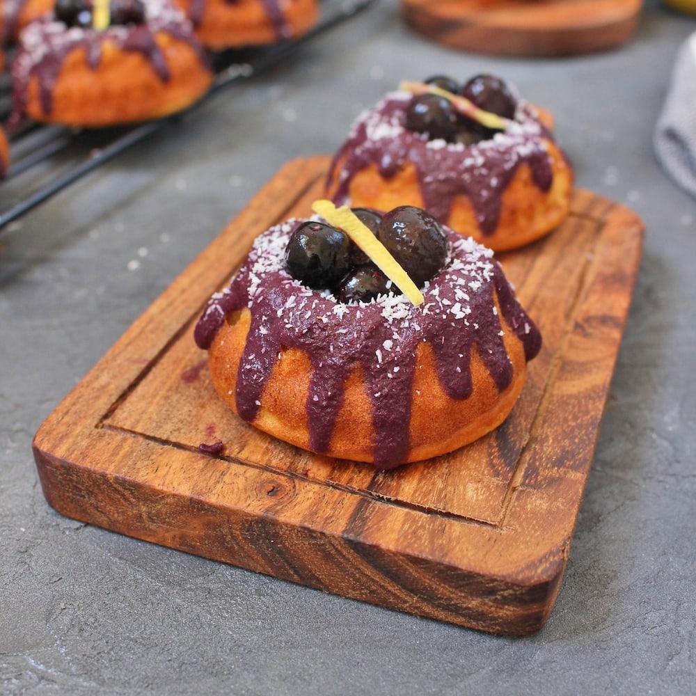 Two Lemon Blueberry Mini Bundt Cakes on a wooden serving board