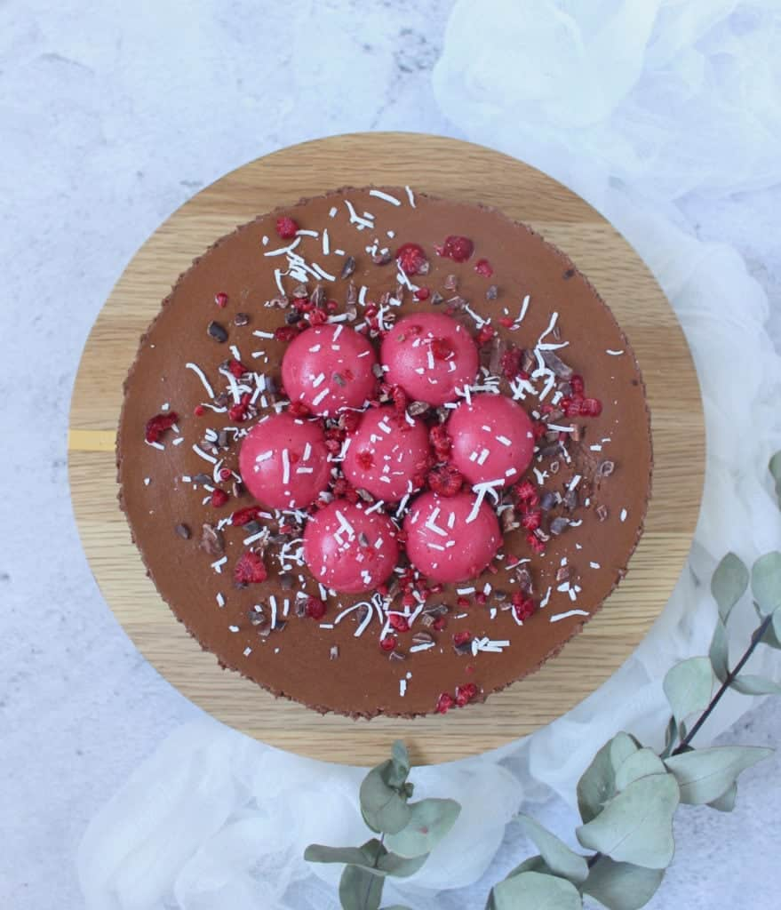 Flatlay photo of the cake on a round wooden board with green leaves