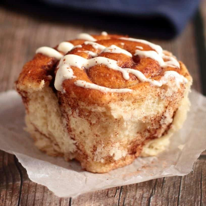One cinnamon roll on a piece of baking paper