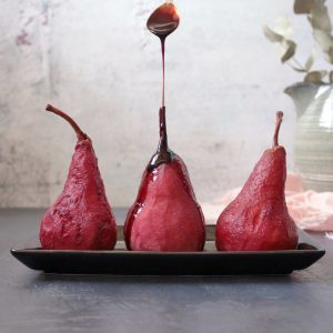 Three Poached Pears on a plate with Poached Syrup