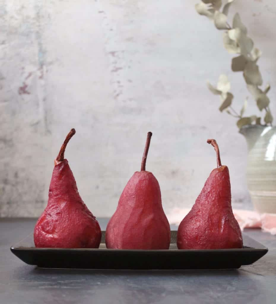 3 Pears standing on a black plate