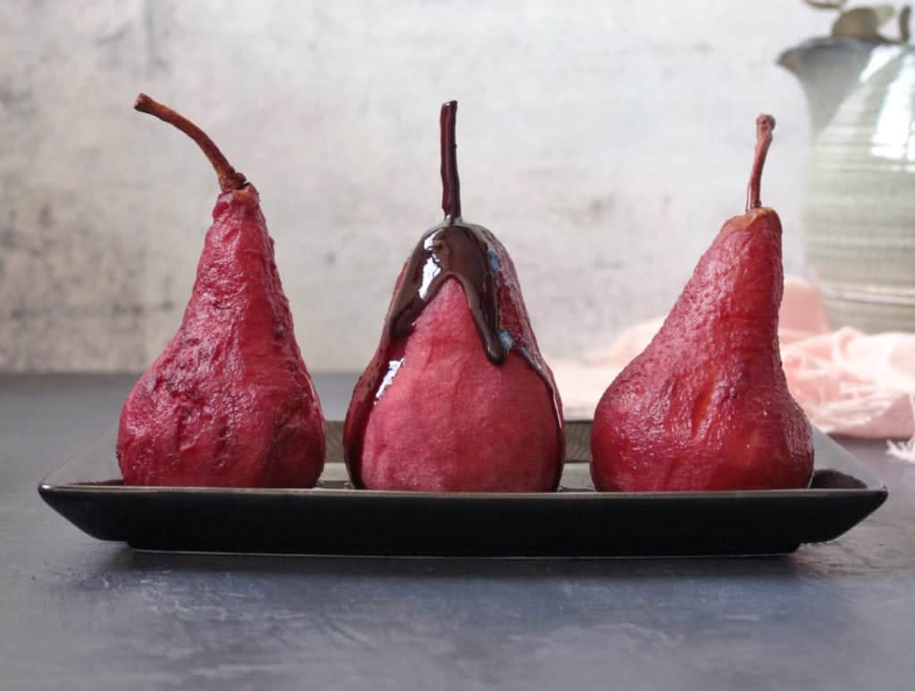 Red wine syrup dripping over a pear