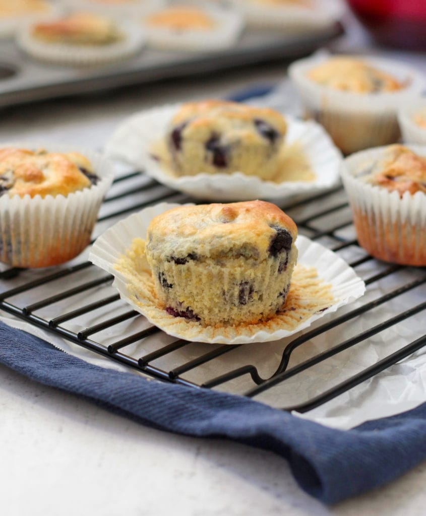 Muffins on a cooling rack over a blue napkin