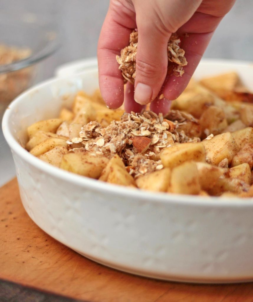 Sprinkling the Oat Crumble over the fruits.