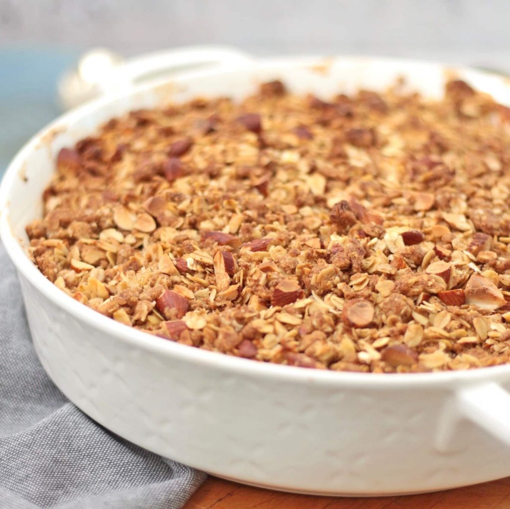 Close up on the baked crumble in a white ceramic dish.