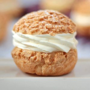 Close up on a choux bun filled with cream over a beige plate