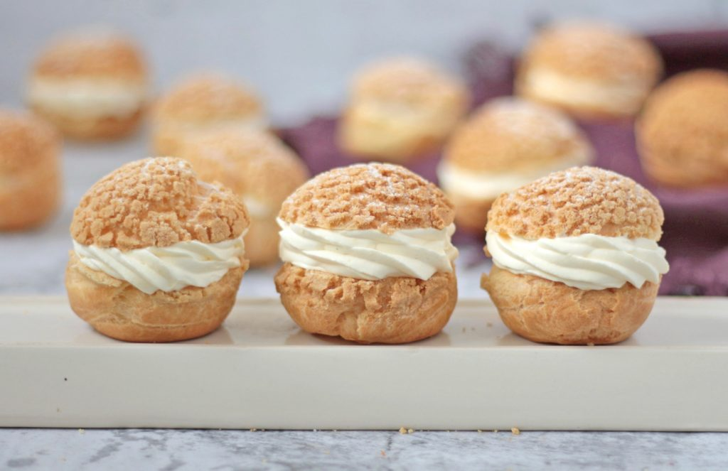 3 Choux Buns filled with cream on a beige plate