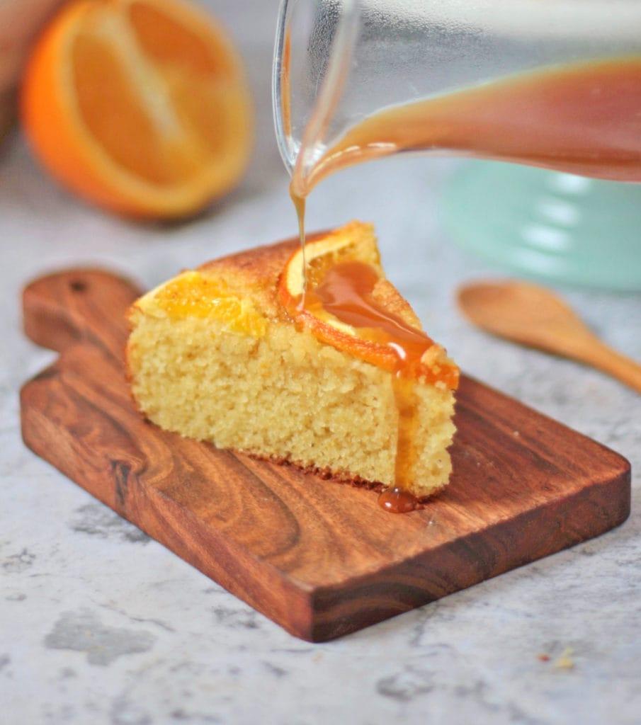 Orange syrup poured over a slice of semolina cake