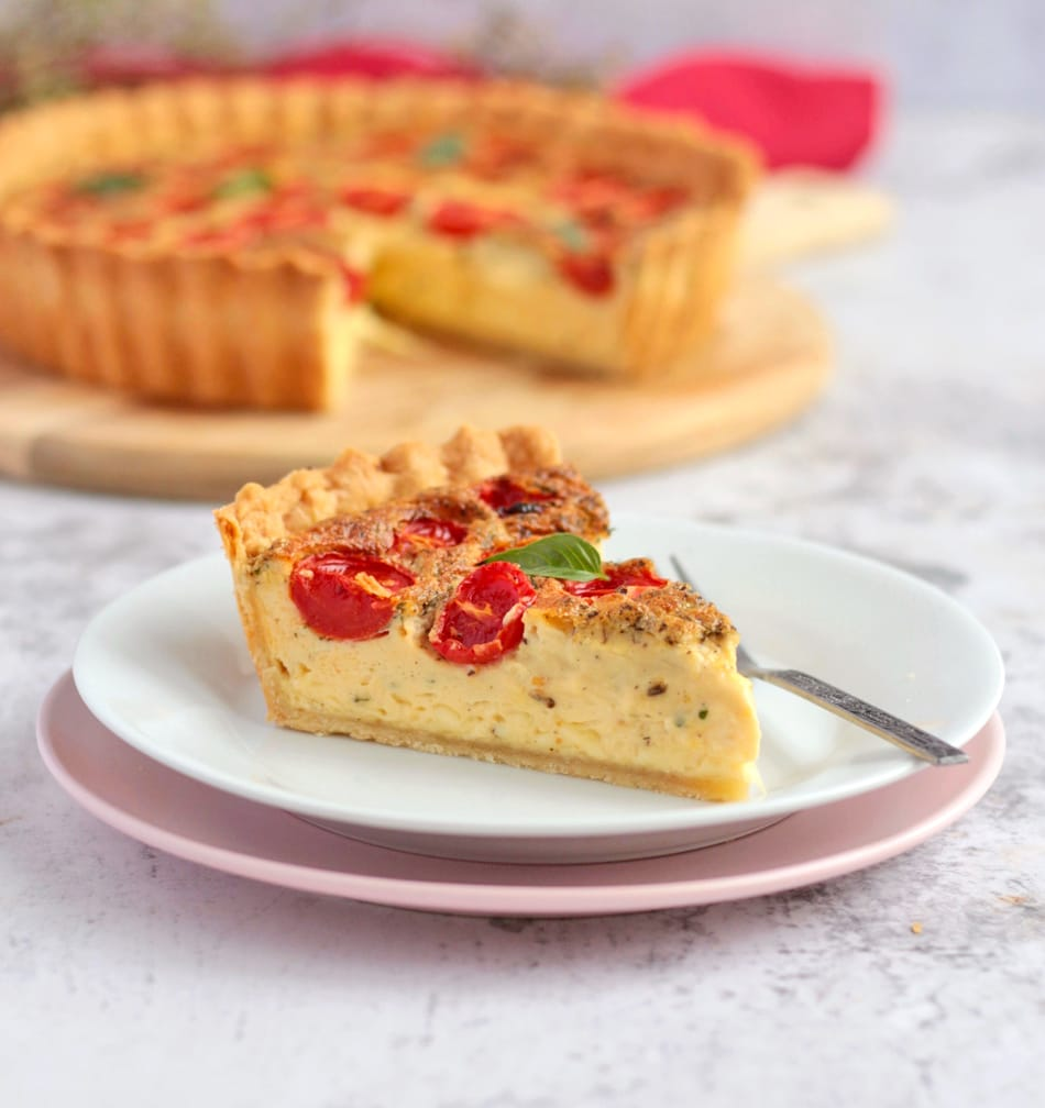 One slice of quiche on a white and pink plate