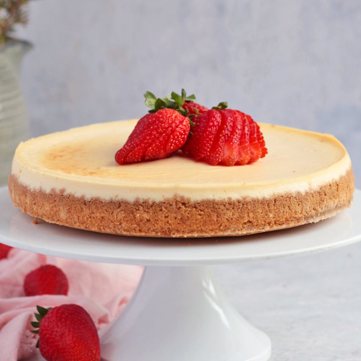 Cheesecake on a white cake stand topped with strawberries