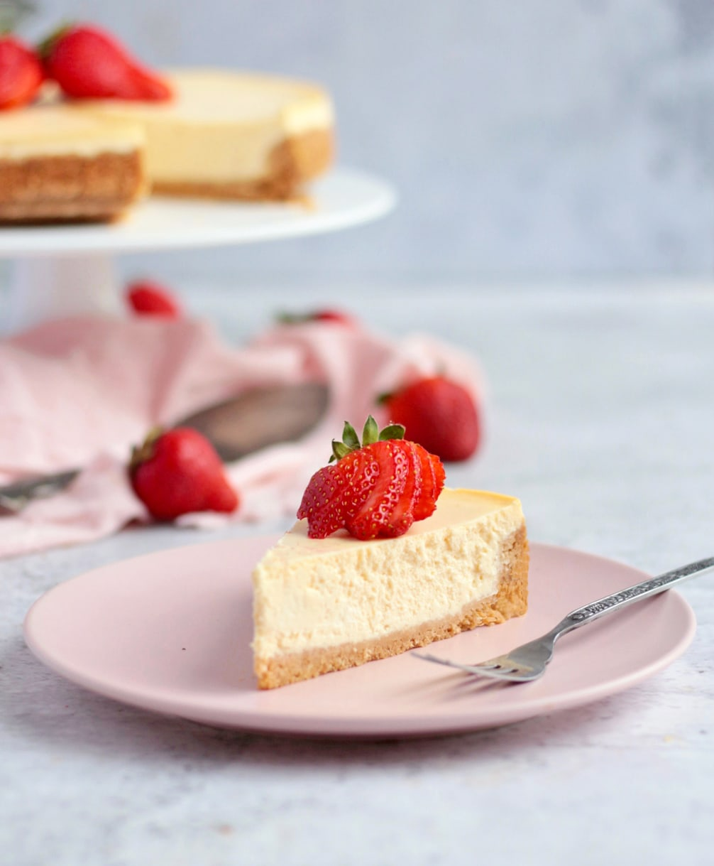 One slice of cheesecake topped with fresh strawberries on a pink plate