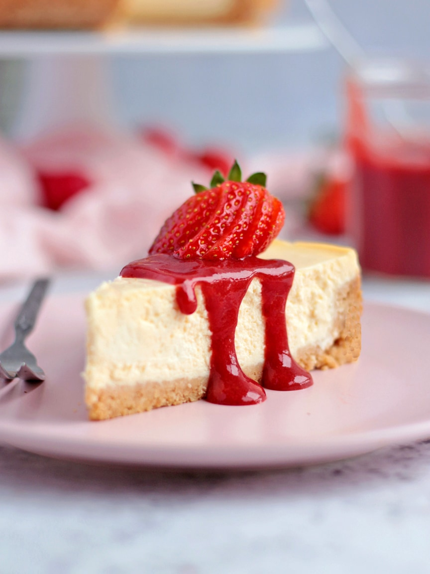One slice of cheesecake topped with the strawberry coulis and a fresh strawberry.