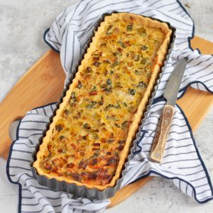 Leek tart in the tart tin on a board