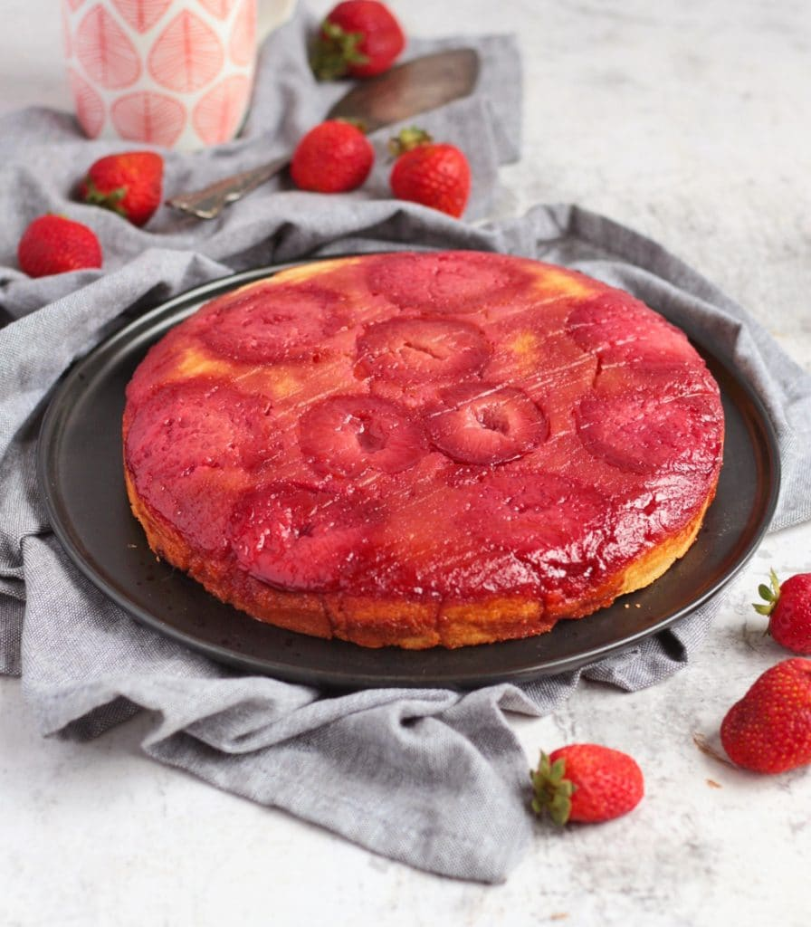 Upside Down Plum Cake on a black plate surrounded by strawberries