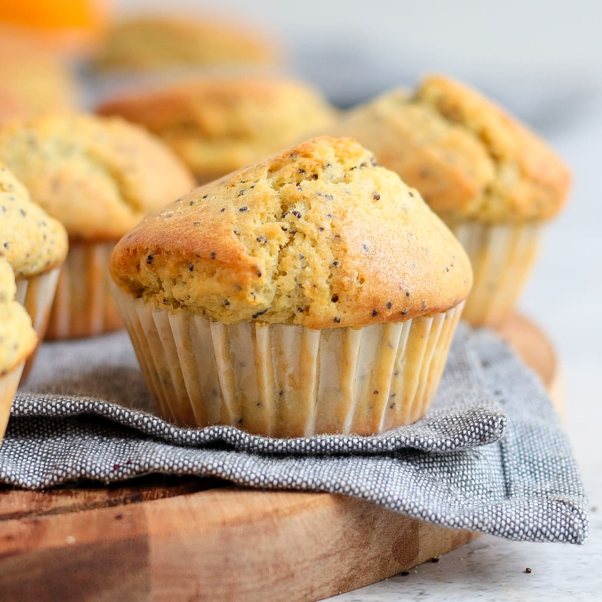 Close up on a muffin over a grey napkin and wooden board.