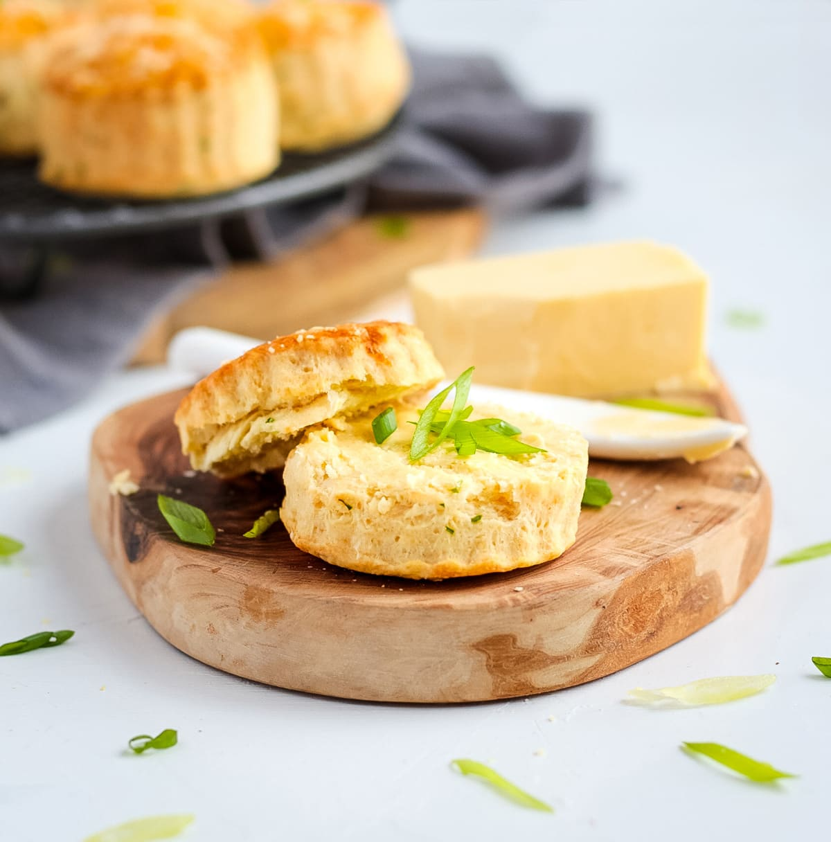 One scone on a wooden tray sliced in half and topped with butter