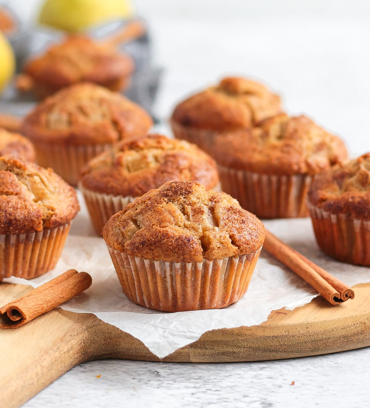 Muffins on a round wooden board with cinnamon sticks