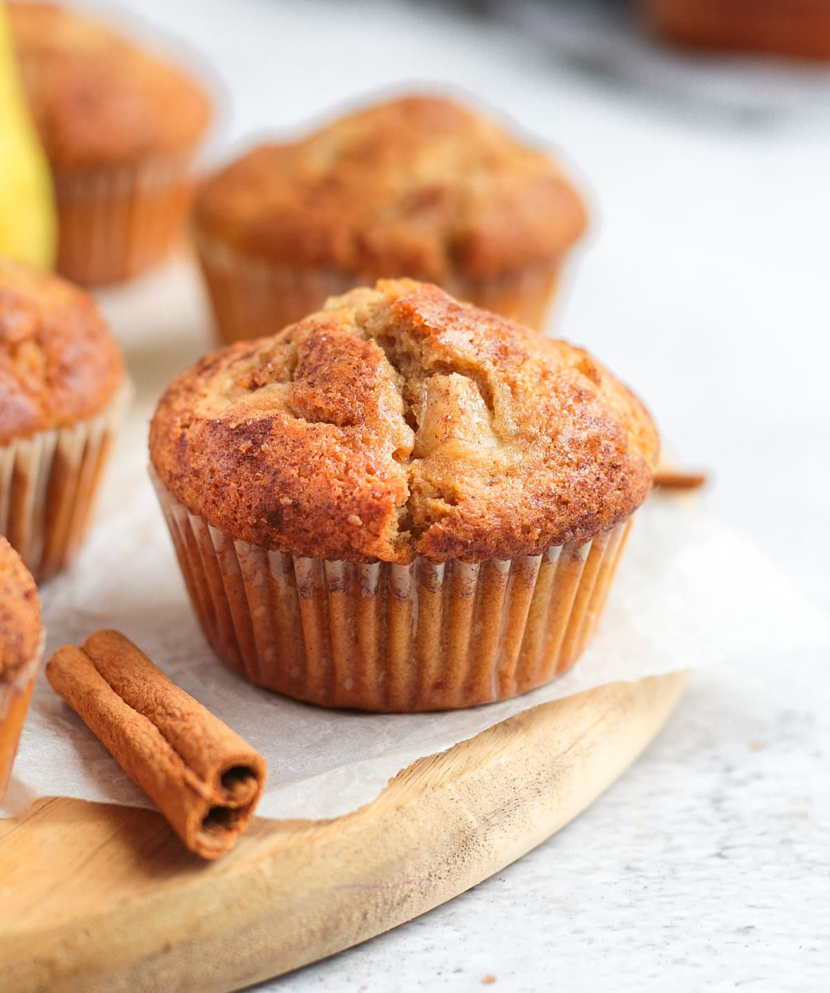 One muffin on a round wooden board over baking paper