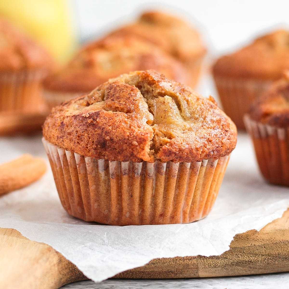 Close up on a pear muffin over baking paper and a wooden board