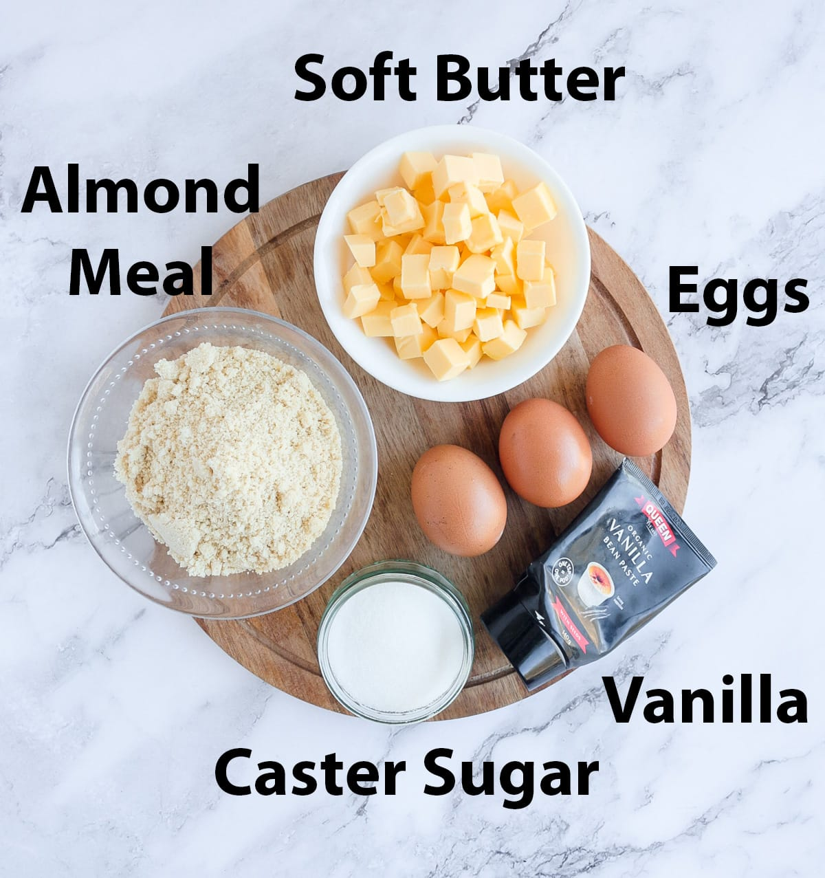 Ingredients place on a round wooden board over a marble surface.
