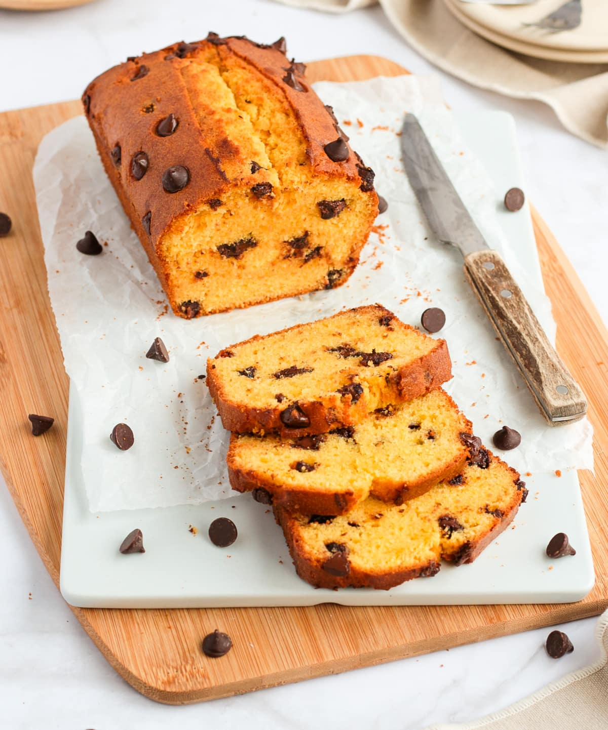 3 slices of cake laying next to the loaf on a white and wooden board