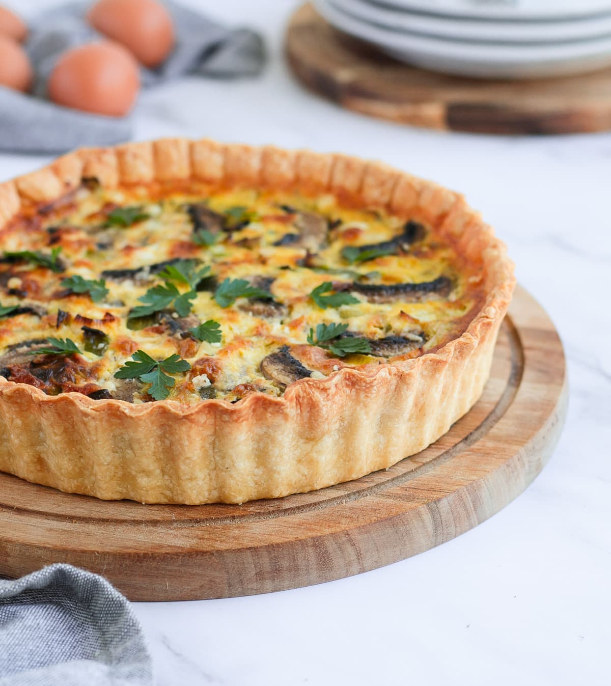 Side view on the quiche over a wooden round board