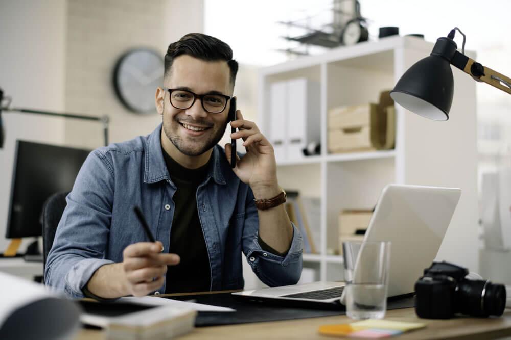 Geschäftsmann im Office. Mann, der am Telefon bei der Arbeit spricht.