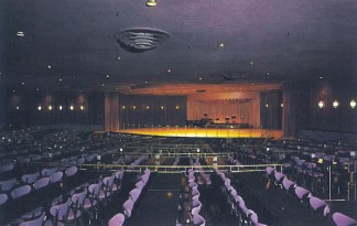 Empty terraced theater seating and a lit stage