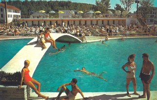 Historic postcard of outdoor pool with bridge over center and lots of people sunbathing on opposite side of pool