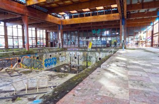 Facing hallway windows from other end of indoor pool room with view of graffitied, empty pool