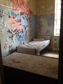 Patient room with two beds and colorful peeling paint on walls