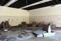 Trashed cafeteria seating with booths torn apart and strewn about