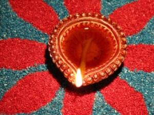 Author: nkjain via Wikipedia Commons रंगबिरंगी रंगोली पर सजा, तेल का जलता हुआ दीया। Burning oil lamp on a colourful rangoli designed on Diwali.