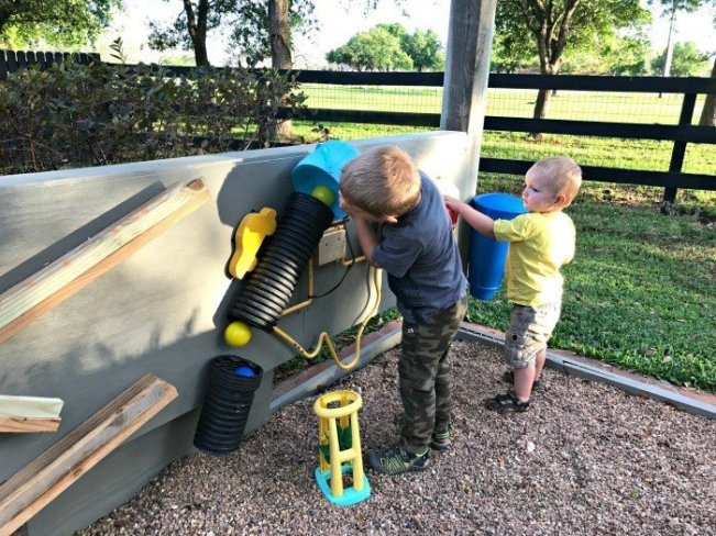 Build this fun and easy pea gravel play area, backyard activity wall, and DIY Rustic Bench. All the fun of a sand box, without the mess.