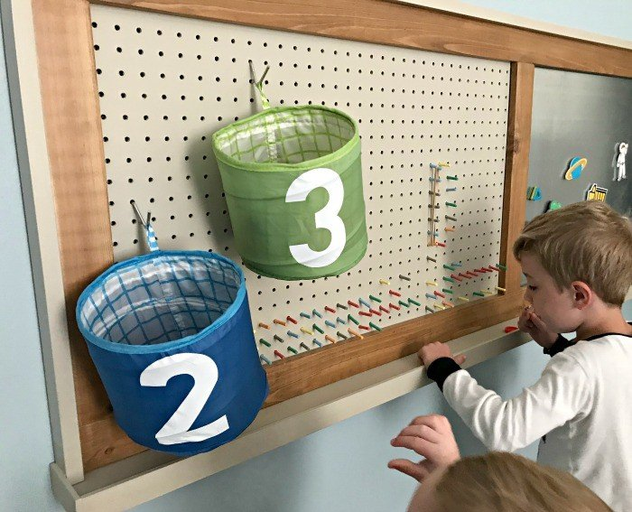 A pegboard with colorful pegs to make designs and bins for basketball hoops. Build a fun DIY Modern Farmhouse Kids Activity Wall Board. With 20 Ideas for board options that work for kids, teens, and adults. #ModernFarmhouse #KidsFurniture #DIYKids #AbbottsAtHome