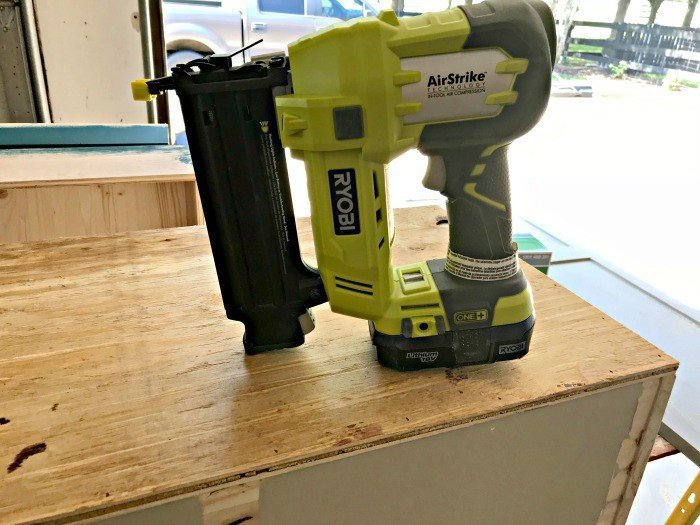 Gluing and nailing the bottom onto the box. Build a Modern Farmhouse DIY Wooden Toy Storage Crate or Box for all of those kids toys cluttering up your house. Makes a beautiful throw pillow and blanket box in a Living Room or catch all storage box for teens too! #AbbottsAtHome #StorageBox #ToyBox #DIYStorage