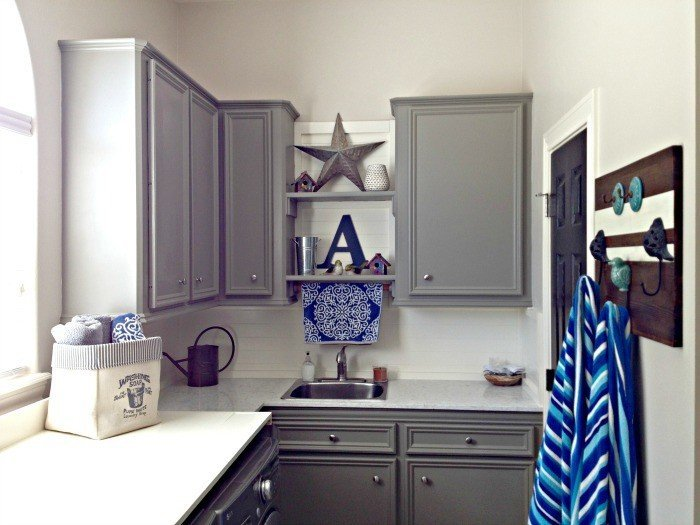 Dark grey cabinets with a white quartz counter in a Laundry Room with blue accents. This DIY Laundry Room Makeover Ideas post is full of Before & After Makeover Photos, budget-friendly DIY ideas, and Laundry Room decor. #LaundryRoom #BeforeandAfter #AbbottsAtHome