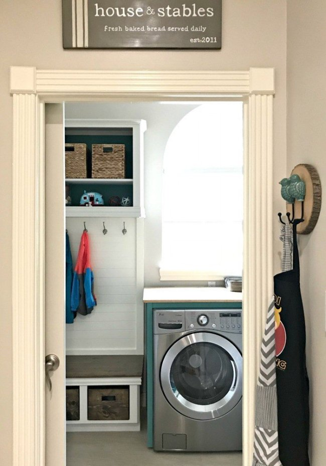 The DIY Mudroom Bench in a Modern Farmhouse look using teal, wood, and lots of white. This Modern Farmhouse Small Laundry Room Design is full of easy DIY projects and affordable decor. #LaundryRoom #ModernFarmhouse #Teal #AbbottsAtHome