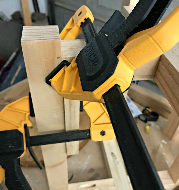 Using Dewalt Clamps and scrap wood to hold pieces in place before screwing in with Kreg Jig.