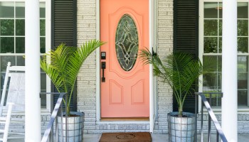 A bright coral front door with two planters filled with palms