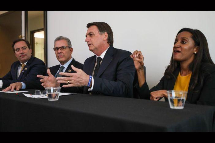 O presidente Jair Bolsonaro, em Dallas (EUA), faz transmissão ao vivo para as redes sociais. ao lado do presidente da Caixa, Pedro Guimarães, do ministro de Minas e Energia, Bento Albuquerque, e da intérprete de libras, Joyce Porto.