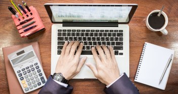 Top view of business man hands working on laptop or tablet pc on wooden desk.