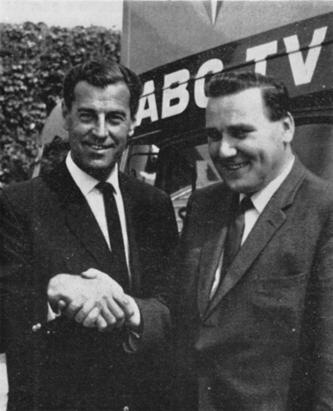 Two men shake hands in front of an OB unit