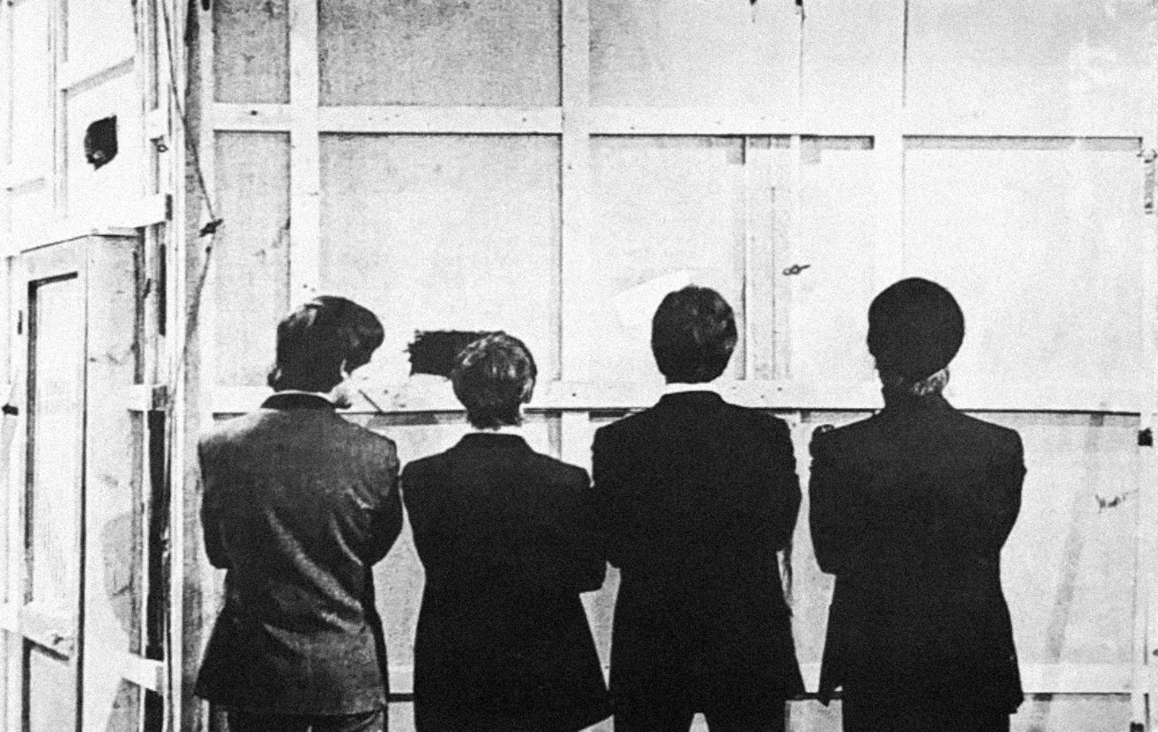 The Beatles facing away from the camera