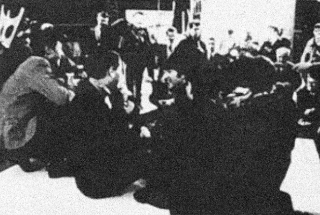 The Beatles and others sit on a stage facing an audience