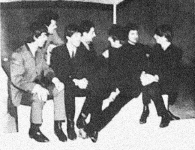 The Beatles sit on a stage with the Winters brothers and Lionel Blair